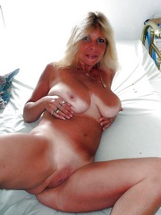 Tanned blonde lies on a bed without..